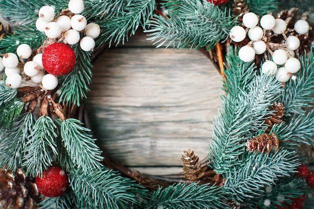 Weihnachtsdekorativer kranz auf dem hölzernen hintergrund horizontal