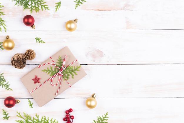 Weihnachtsdraufsicht der geschenkbox mit fichtenzweigen, kiefernkegeln, roten beeren auf hölzernem bac