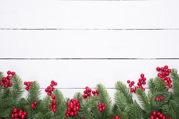 Weihnachtsdraufsicht von fichtenzweigen, kiefernkegeln, rote beeren auf holztischhintergrund.