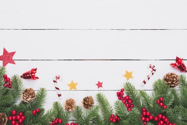 Weihnachtsdraufsicht von fichtenzweigen, kiefernkegeln, roten beeren und glocke