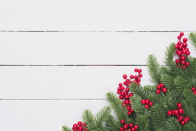 Weihnachtsdraufsicht von fichtenzweigen, rote beeren auf holztischhintergrund.