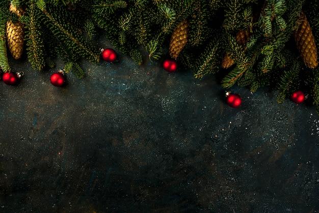 Weihnachtsdunkelblauer hintergrund mit tannenbaumasten, kiefernkegeln und christbaumkugeln kopieren raum oben