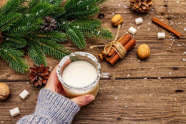 Weihnachtseierlikör oder cola de mono cocktail. klassisches wintergetränk im glasbecher, weihnachtsdekorationen. frauenhand in trikot.