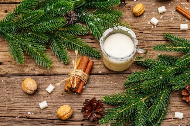 Weihnachtseierlikör oder cola de mono cocktail. klassisches wintergetränk im glasbecher, weihnachtsdekorationen. immergrüne zweige, zimt, walnüsse, zucker.