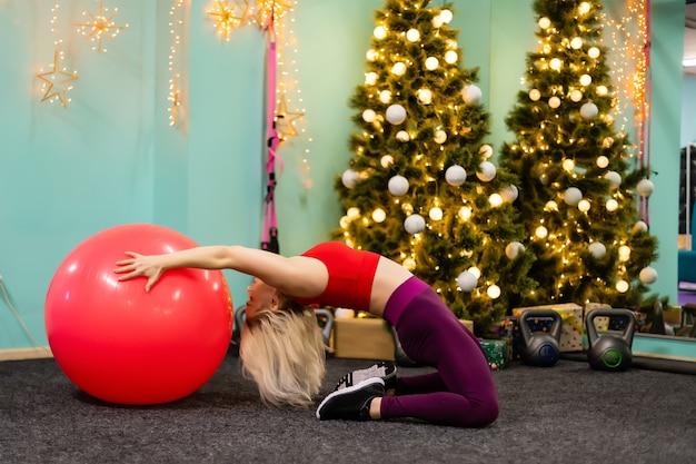 Weihnachtseignungfrau auf dem übungsball, der froh und glücklich lächelt. schönes fröhliches kaukasisches weibliches fitnessmodell in der nähe des weihnachtsbaums im fitnessstudio