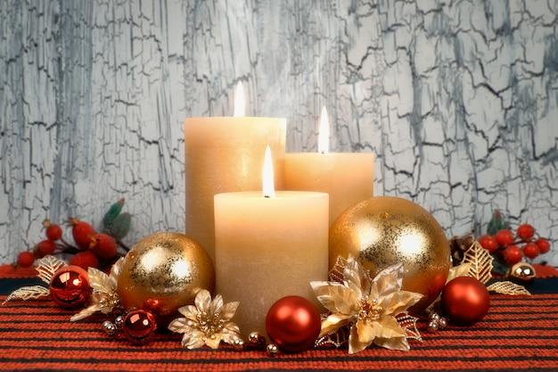 Weihnachtseinführungskerzen mit den goldenen und roten dekorationen