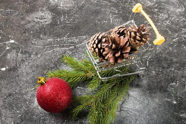 Weihnachtseinkäufe, einkaufswagenminiatur mit zapfen und weihnachtsdekor, schwarzer hintergrund, kopierraum