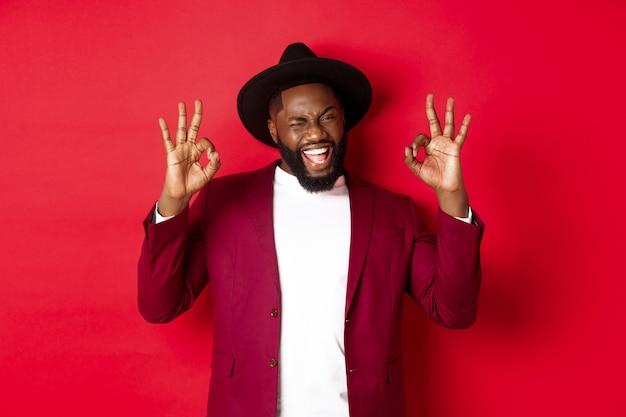 Weihnachtseinkäufe und menschenkonzept. gut aussehender schwarzer mann, der mit vertrauen, garantie oder zustimmung ein okay-zeichen zeigt und ja sagt, auf rotem hintergrund steht.