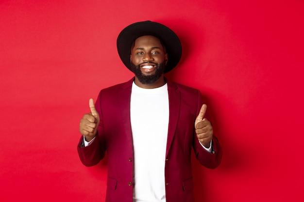 Weihnachtseinkäufe und menschenkonzept. schöner schwarzer mann, der zufrieden lächelt, daumen hoch zeigt, wie und zustimmt, etwas genehmigen, vor rotem hintergrund stehend