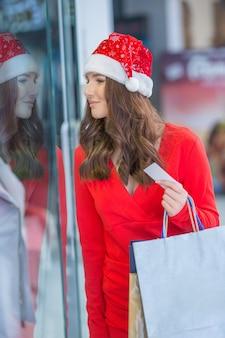 Weihnachtseinkauf. attraktives glückliches mädchen mit kreditkarte und einkaufstaschen in sankt-hut.