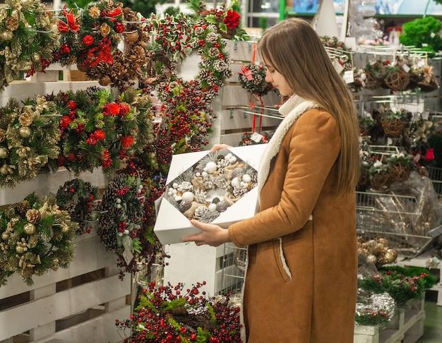 Weihnachtseinkauf. weihnachtskranz auf weiblichen händen