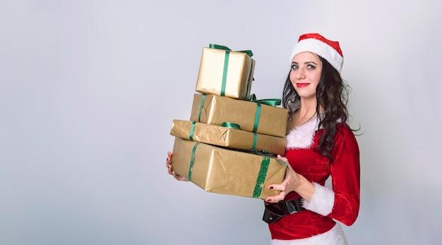 Weihnachtseinkaufsfrau, die viele weihnachtsgeschenke in ihren armen trägt, die sankt-hut tragen. schönes junges weibliches modell auf grauem hintergrund. mädchen gekleidet santa gibt geschenke