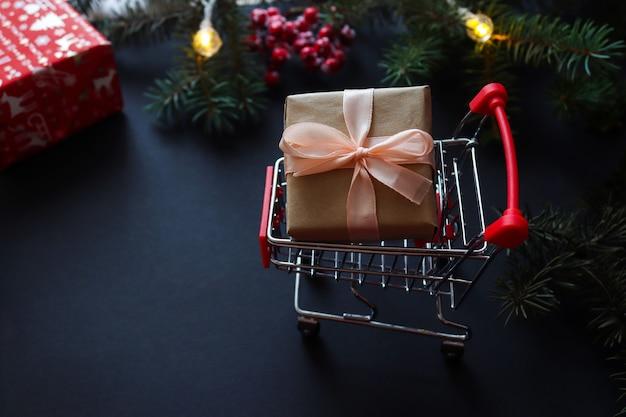 Weihnachtseinkaufskonzept. lebensmittelwagen und geschenk auf schwarz