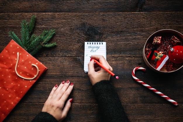 Weihnachtseinkaufsliste weihnachtseinkäufe auf budget weihnachtsgeld sparen tipps weibliche hände mit