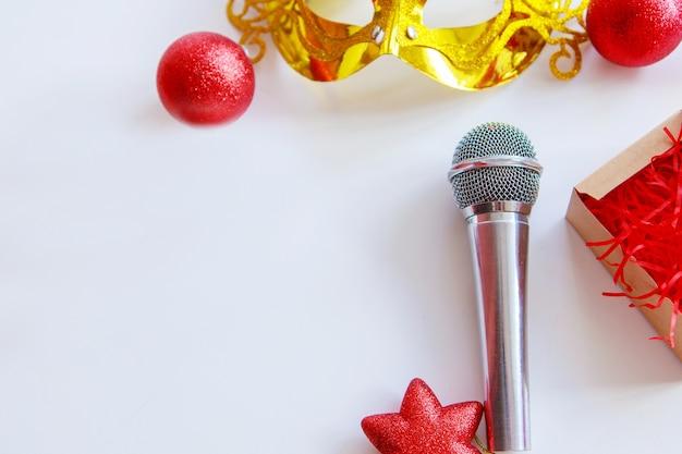 Weihnachtseinkaufsmikrofon goldene maske und weihnachtsspielzeug musikalische kreativität im neuen jahr lokalisiert auf einem weißen hintergrund