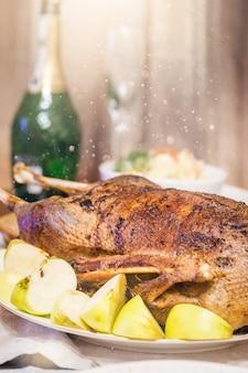 Weihnachtsentenbraten mit äpfeln auf einem festlich gedeckten tisch