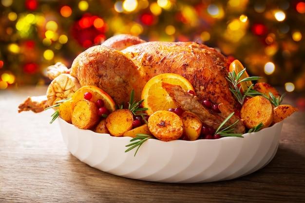 Weihnachtsessen. gebackener truthahn garniert mit kartoffeln, orangen und preiselbeeren auf einem holztisch
