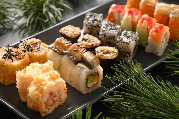 Weihnachtsessen mit sushi eingestellt mit weihnachtsdekoration auf schwarzem hintergrund. nahansicht. weihnachts- oder neujahrsparty.