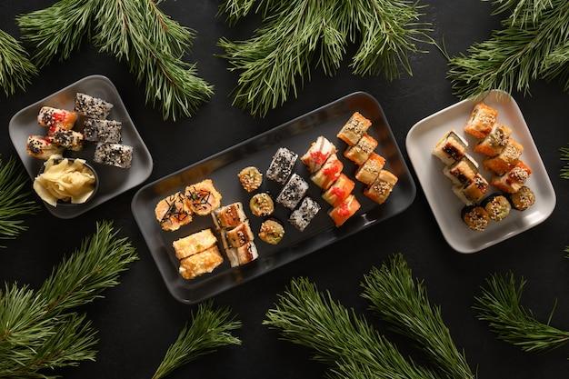 Weihnachtsessen mit sushi eingestellt mit weihnachtsdekoration auf schwarzem hintergrund. von oben betrachten. neujahrsparty.