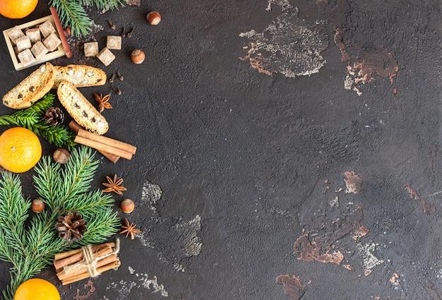 Weihnachtsessen mit tannenzweigen, wintergewürzen, clementinen und biscotti