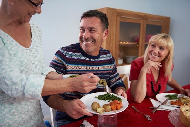 Weihnachtsessen serviert von der ältesten frau der familie