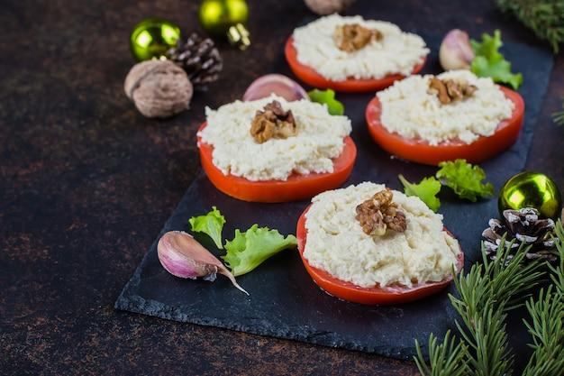 Weihnachtsessen tabelleneinstellung. köstliche snack-tomate mit geriebenem käse mit knoblauch auf dunkler steintabelle. draufsicht, kopie, raum. festliche dekoration, tannenzweig