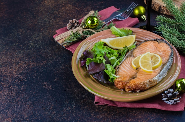 Weihnachtsessen tabelleneinstellung. köstliches lachssteak grillte auf platte mit zitrone und sortiertem salat auf dunkler steintabelle. draufsicht, kopie, raum