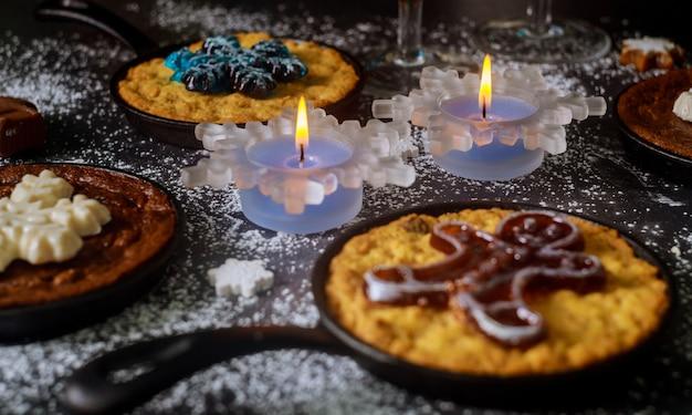 Weihnachtsessen tisch mit brennenden kerzen, gläsern und vier mini pie