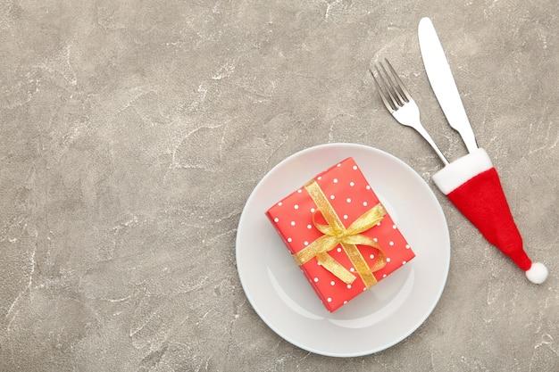 Weihnachtsessenhintergrund mit rotem geschenk auf grauer ansicht von oben draufsicht