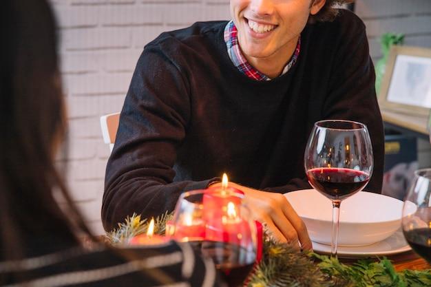 Weihnachtsessenkonzept mit wein und lächelndem mann