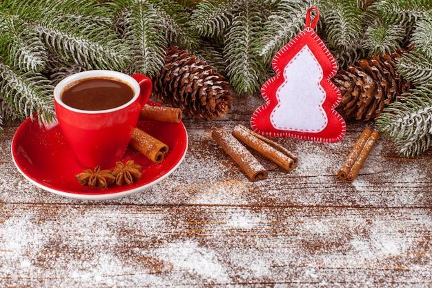 Weihnachtsfahne mit grünem baum, zapfen, rote schale mit heißer schokolade, handgemachte filzdekorationen