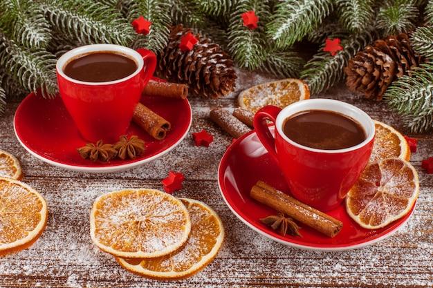 Weihnachtsfahne mit grünem baum, zapfen, roten tassen mit heißer schokolade, orange und zimt.