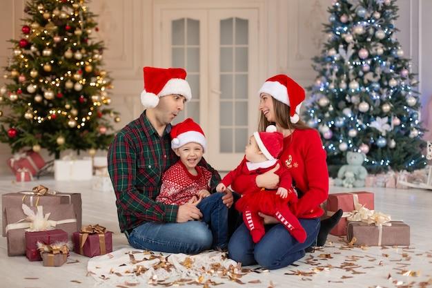 Weihnachtsfamilie glückliche mama, papa und kleine tochter und sohn auf weihnachtsmann-hut. genießen sie liebesumarmungen, feiertagsleute. weihnachtsbaum mit girlanden im dekorierten raumhintergrund. zusammengehörigkeitskonzept