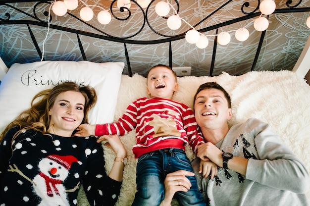 Weihnachtsfamilie! glückliche mutter, vater und kleiner sohn in weihnachtsmannpullovern, liegend. liebe umarmungen genießen, urlaub menschen. zusammengehörigkeitskonzept. flach liegen. draufsicht.