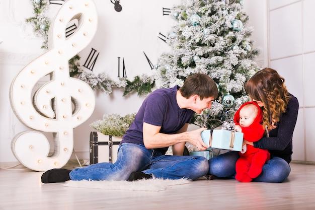Weihnachtsfamilie mit babyöffnungsgeschenken. glücklich lächelnde eltern und kind zu hause feiern neujahr