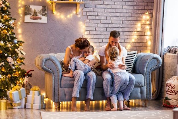 Weihnachtsfamilie mit zwei kindern im schönen wohnzimmer