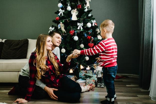 Weihnachtsfamilie offen geschenk geschenkbox, nacht weihnachten. frohe weihnachten und schöne feiertage! familie, die geschenke austauscht. eltern und kleine kinder in der nähe von weihnachtsbaum drinnen.