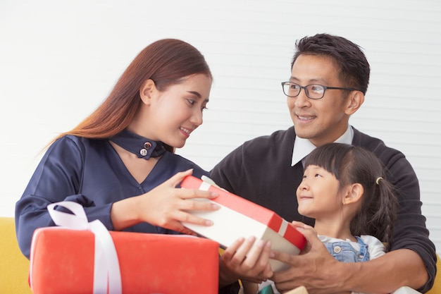 Weihnachtsfamilie und frohe feiertage. mutter und vater, die anwesendes geschenk mit kindern am weißen wohnzimmer halten.
