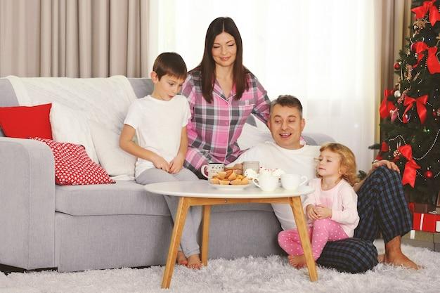 Weihnachtsfamilienporträt beim frühstück im hauptferienwohnzimmer am morgen
