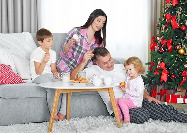Weihnachtsfamilienporträt beim frühstück im wohnzimmer zu hause, am morgen