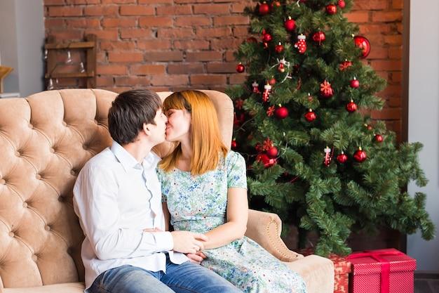 Weihnachtsfamilienporträt im hauptferien-wohnzimmer, haus, das durch weihnachtsbaumkerzen-girlande verziert