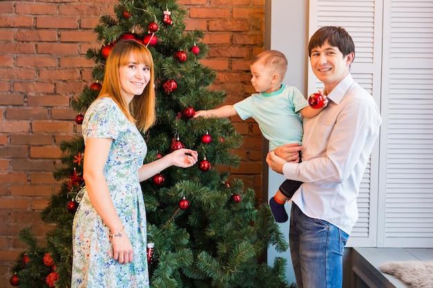 Weihnachtsfamilienporträt im hauptferien-wohnzimmer, kinder und baby an der weihnachtsmütze mit geschenkbox, hausdekoration durch weihnachtsbaumkerzen-girlande
