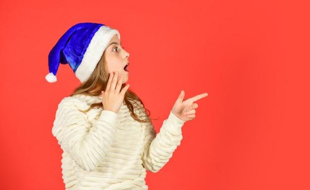Weihnachtsfeier einladung. entzückende mädchen tragen weihnachtsmann-hut roten hintergrund. emotionaler gesichtsausdruck. glückliche kindheit. tage zählen bis weihnachten. weihnachtsfeier. kann emotionen nicht zurückhalten.