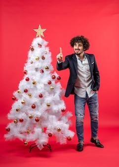 Weihnachtsfeier mit bärtigem jungen mann, der einen zeigt und nahe weihnachtsbaum steht