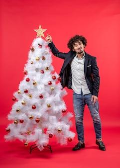 Weihnachtsfeier mit dem glücklichen lustigen jungen mann, der stern zeigt