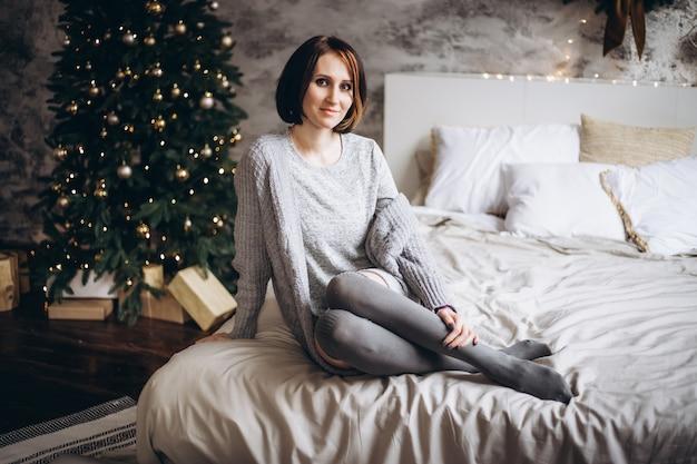 Weihnachtsfeier mit frau auf bett zu hause auf weihnachtszeit