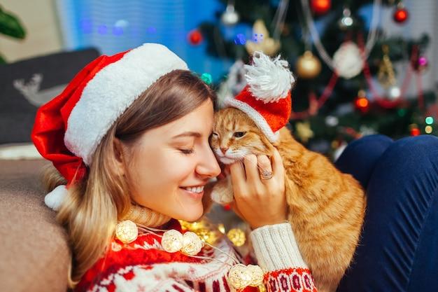 Weihnachtsfeier mit katze. frau, die zu hause haustier in sankt hut durch baum des neuen jahres spielt und umarmt.
