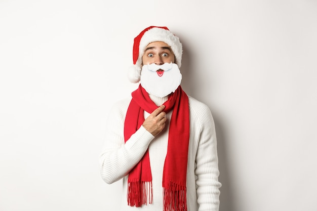 Weihnachtsfeier und feierkonzept. lustiger junger mann in nikolausmütze, der weiße bartmaske hält und gesichter macht, neujahr genießt, weißer hintergrund.