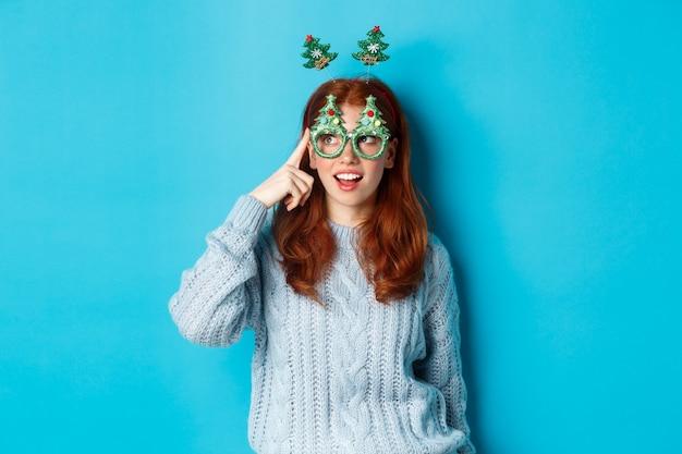 Weihnachtsfeier und feierkonzept. süßes rothaariges teenie-mädchen, das neujahr feiert, weihnachtsbaum-stirnband und lustige brille trägt, amüsiert nach links schaut, blauer hintergrund
