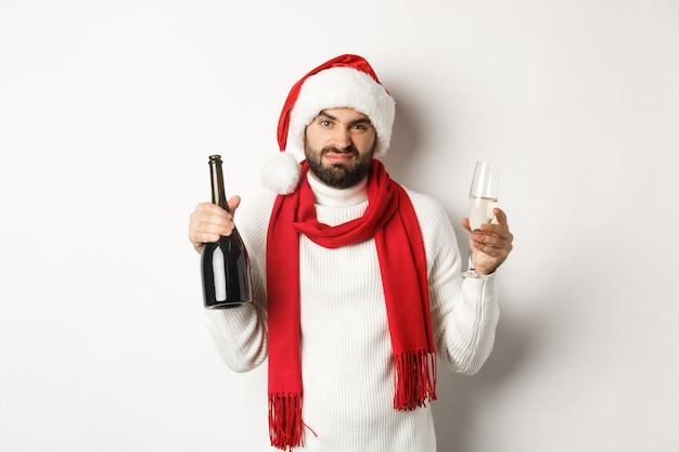 Weihnachtsfeier und feiertagskonzept. skeptischer bärtiger mann in weihnachtsmütze und schal, der champagner hält und sich beschwert, vor weißem hintergrund stehend